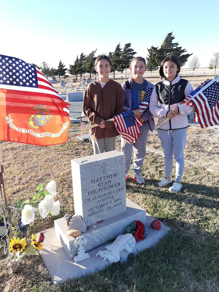 Three students honor our Veterans by putting out flags at the cemetery