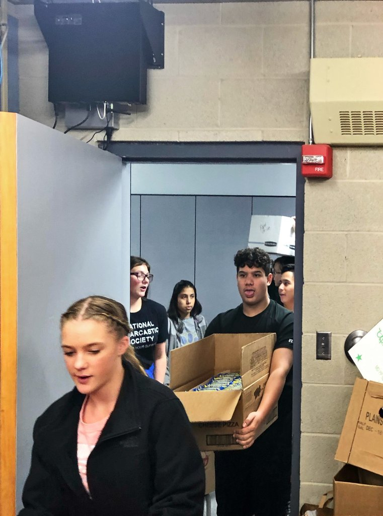 Students carrying in boxes of food for donation