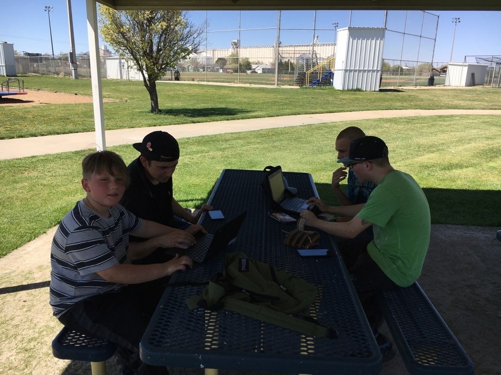 Students working on homework at the park.